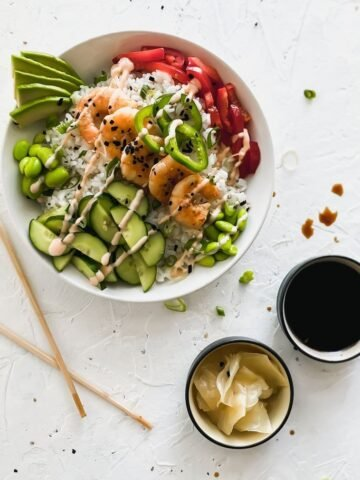 shrimp sushi bowl with chopsticks, sushi ginger, and soy sauce on the side