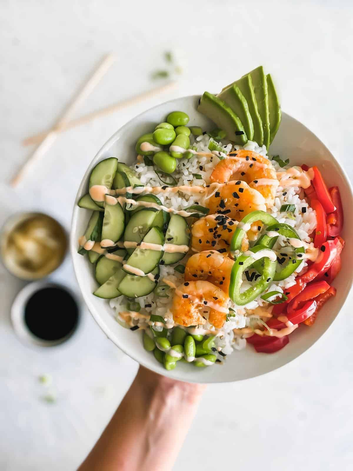 shrimp poke bowl raised in the air with chopsticks, sushi ginger, and soy sauce in background