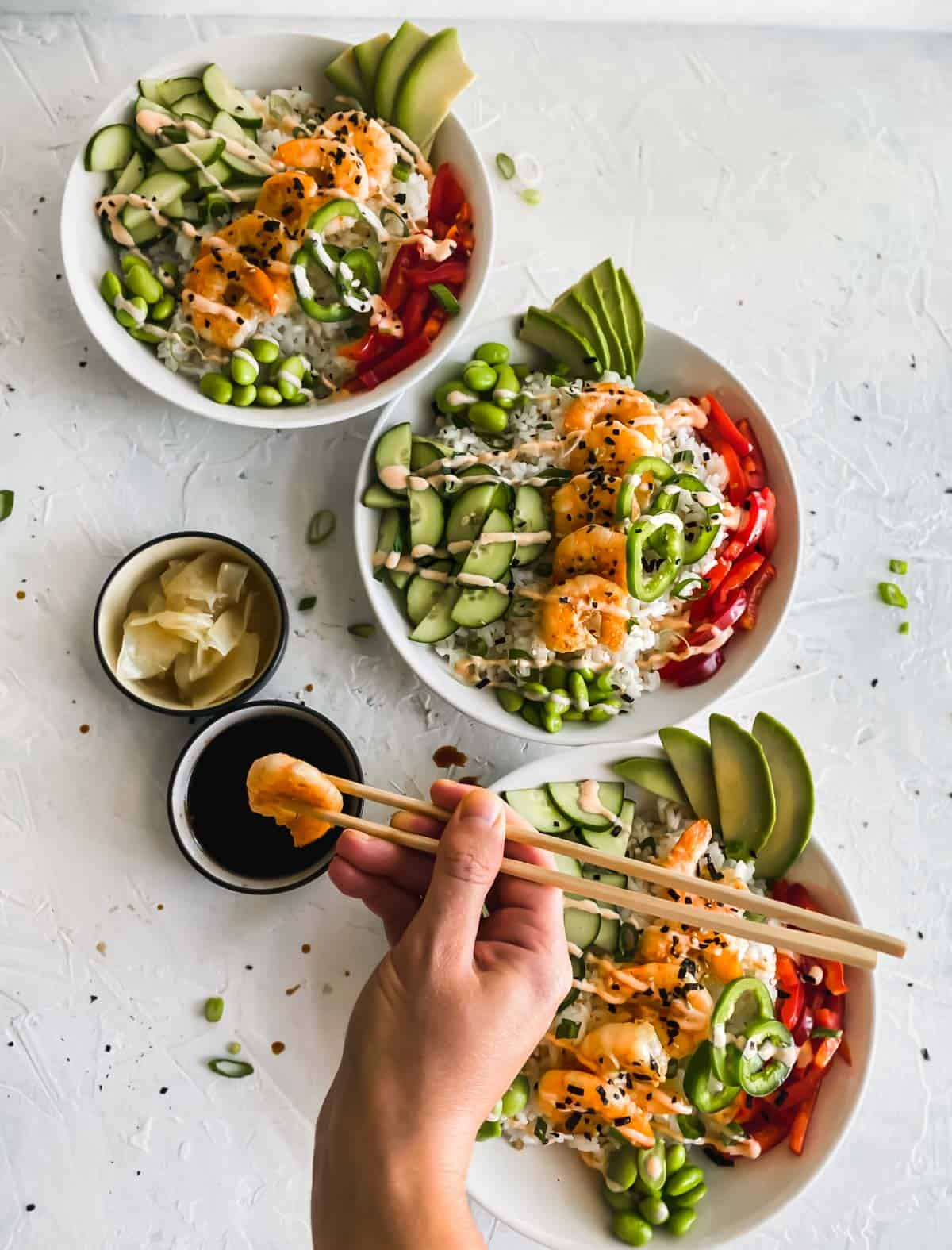 Shrimp Poke Bowls and a hand holding chopsticks with a piece of shrimp dunked in soy sauce