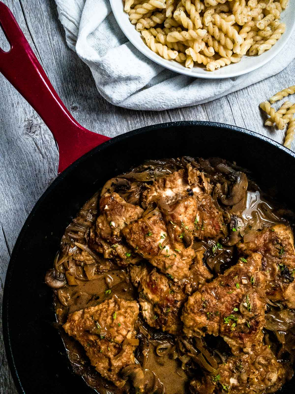 Chicken Marsala in a cast iron skillet with a side of pasta