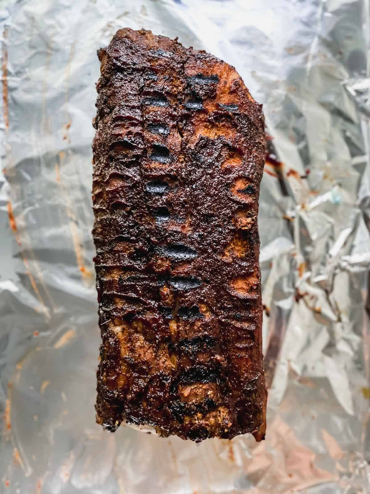 grilled slab of ribs on a sheet pan covered with aluminum foil