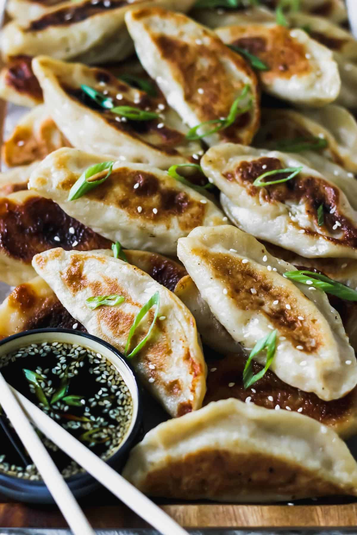 Close up of chinese chicken dumplings with sesame soy sauce and scallions.