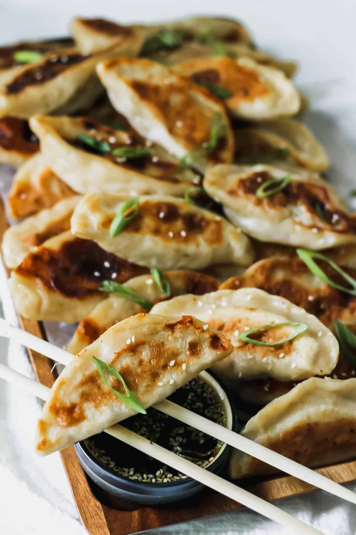 Chinese chicken dumplings with sesame soy sauce on a wooden tray with a white napkin behind it.
