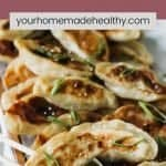 Pinterest pin for chinese chicken dumplings with sesame soy sauce.