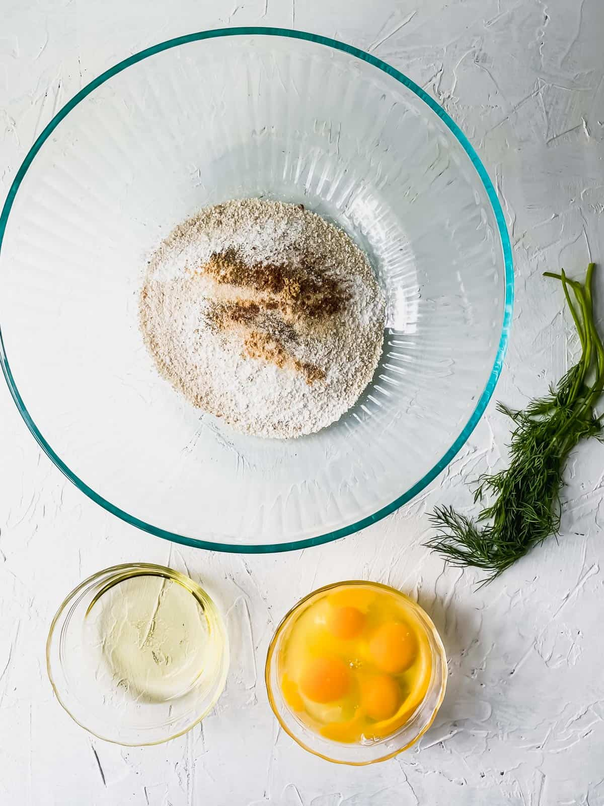 matzo ball dry ingredients in a glass bowl with eggs, oil, and dill on the side