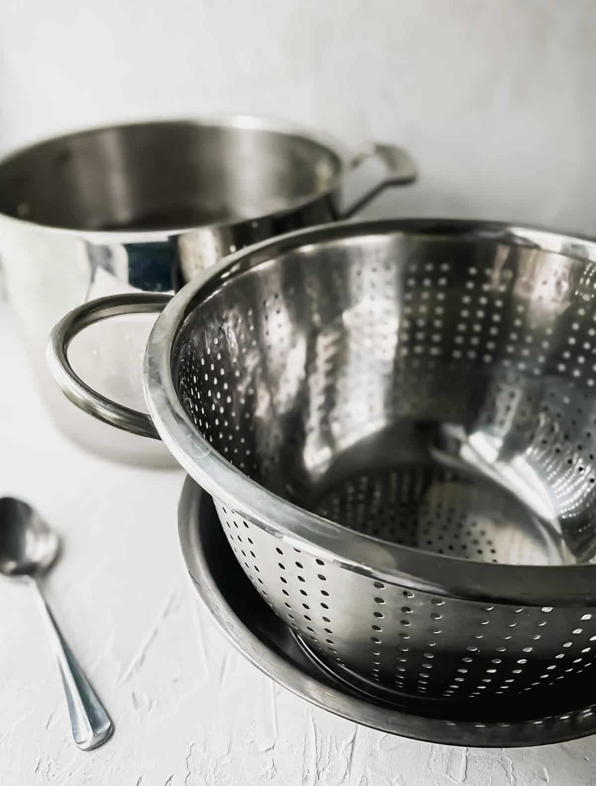 metal colander inside a metal bowl