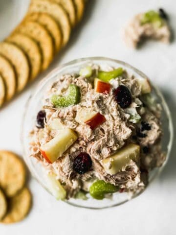 chicken salad in a glass bowl with crackers around it