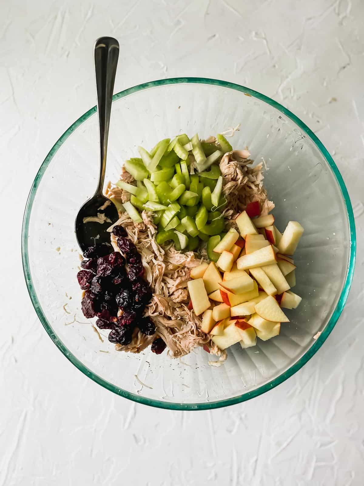 shredded chicken and diced apples and celery in a glass bowl with dried cranberries