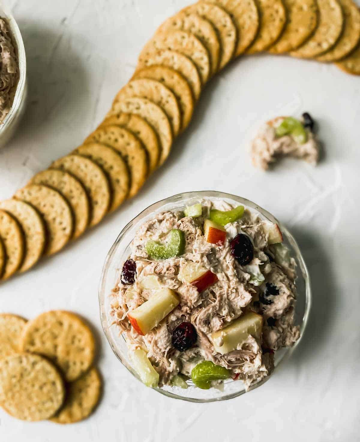 shredded chicken salad with cranberries and apples in a glass bowl with crackers around it