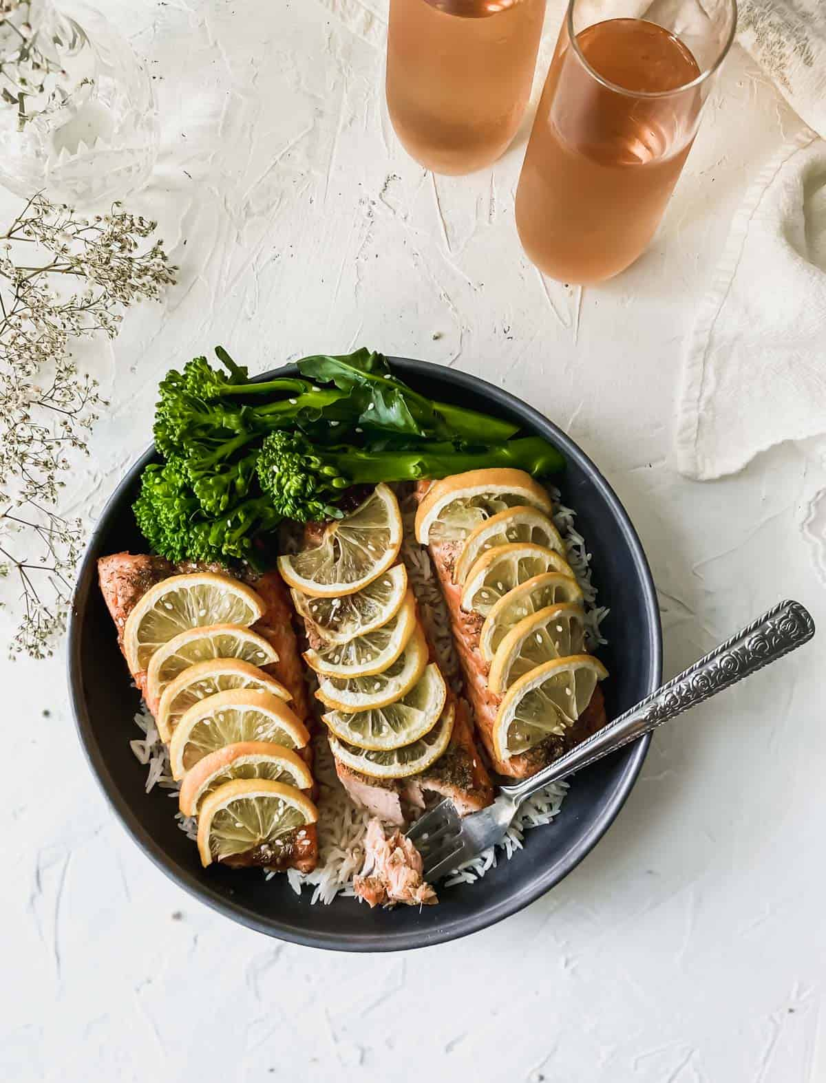 baked teriyaki salmon in a black bowl with 2 glasses of rosé wine next to it.