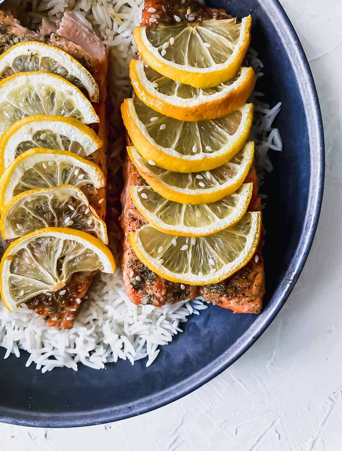 teriyaki salmon with lemon slices on top on a bed of rice in a black bowl.