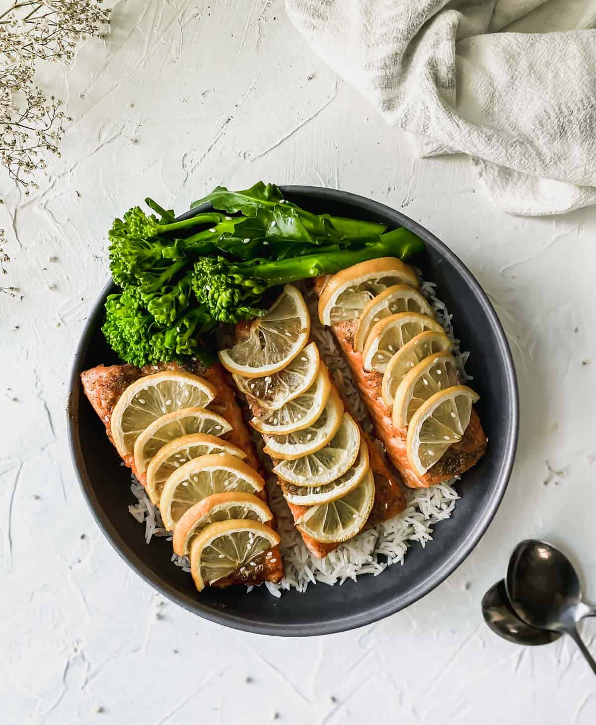 black bowl full of white rice, broccoli, and salmon with 2 spoons below it.