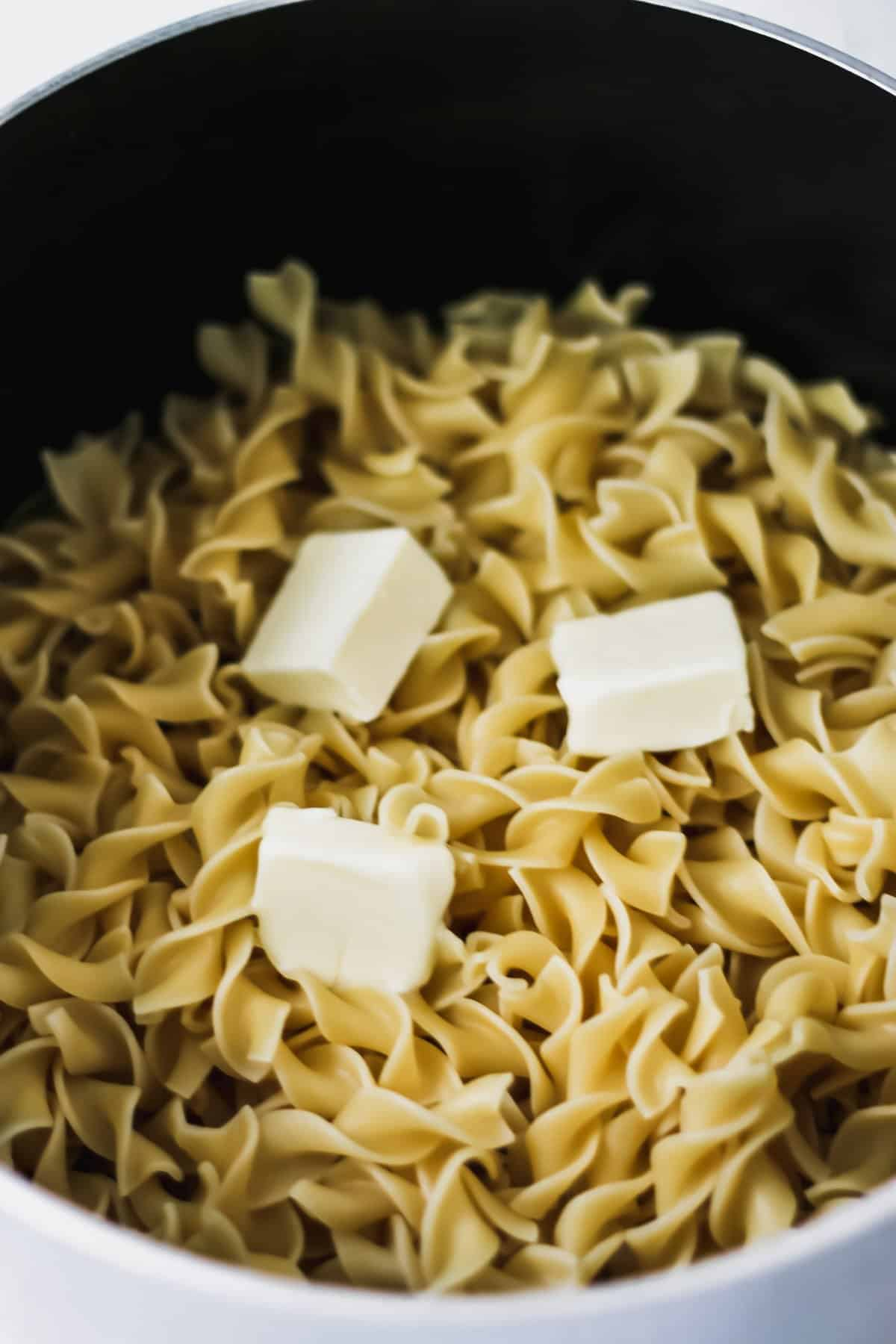 Cooked egg noodles with 3 pads of butter on top.