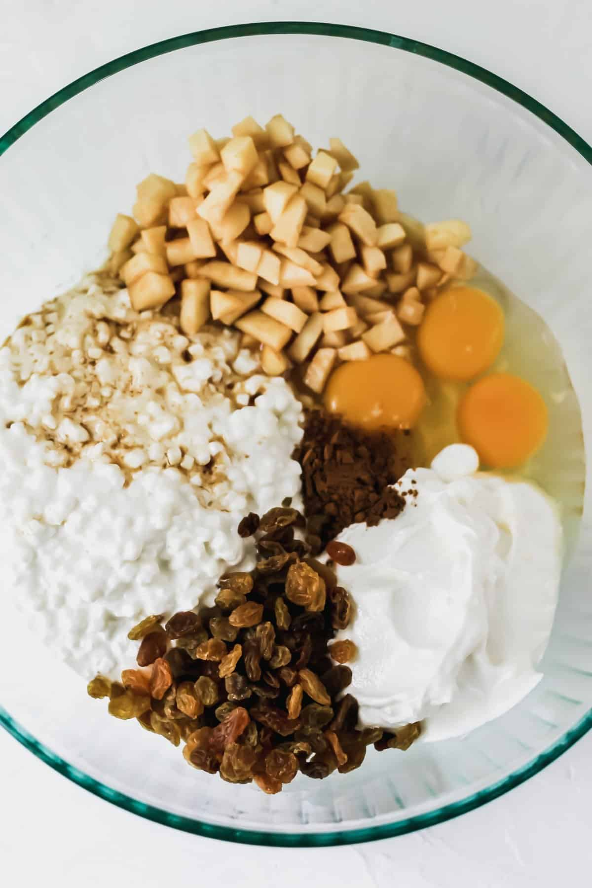 Sour cream, cottage cheese, vanilla, raisins, eggs, cinnamon, and chopped apples in a glass mixing bowl.