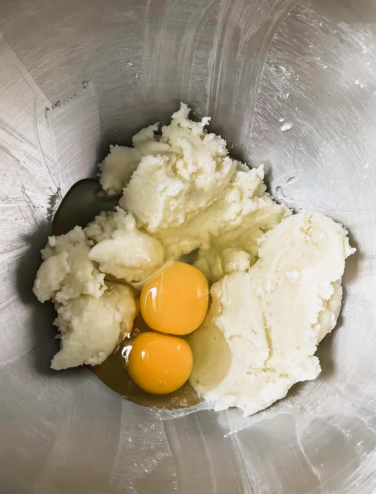 Beaten butter and sugar in a mixing bowl with 2 cracked eggs on top.