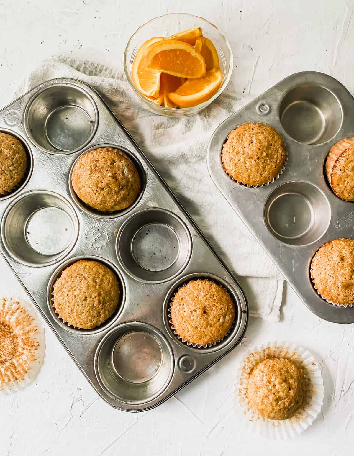 Spiced orange muffins in muffin pans with orange slices next to them.
