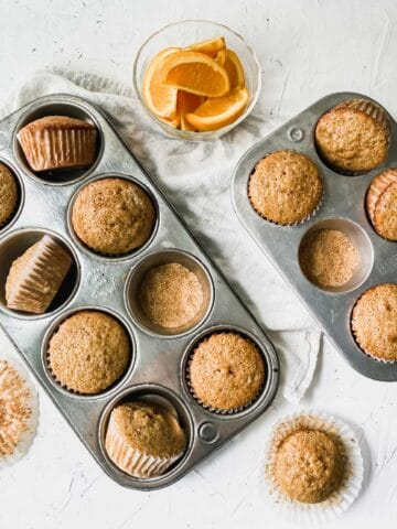 spiced orange muffins in muffin pans with coarse sugar and orange slices around them