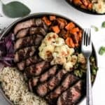 Glazed balsamic steak and veggie bowls with red wine, a fork, and brussels sprout leaves around it.