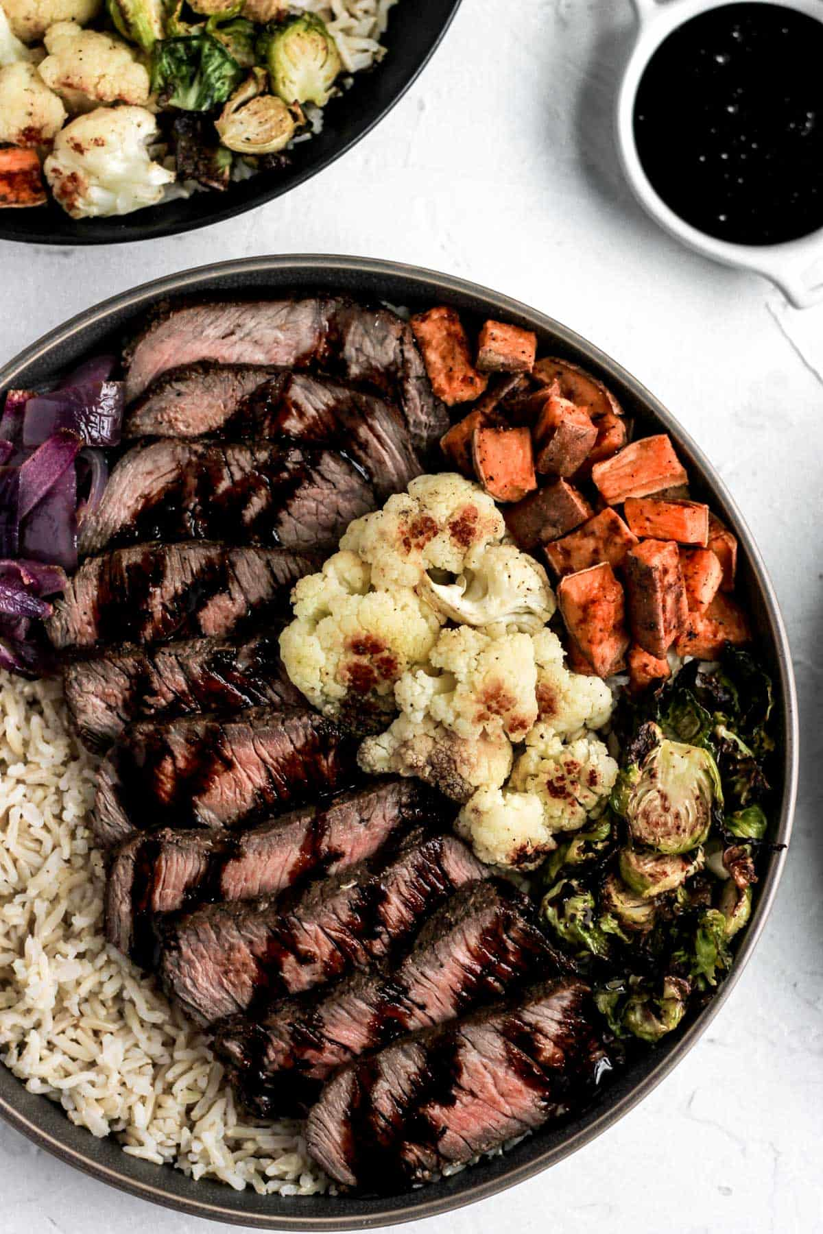 Glazed balsamic steak and veggies over brown rice in a dark gray bowl with a side of balsamic reduction.
