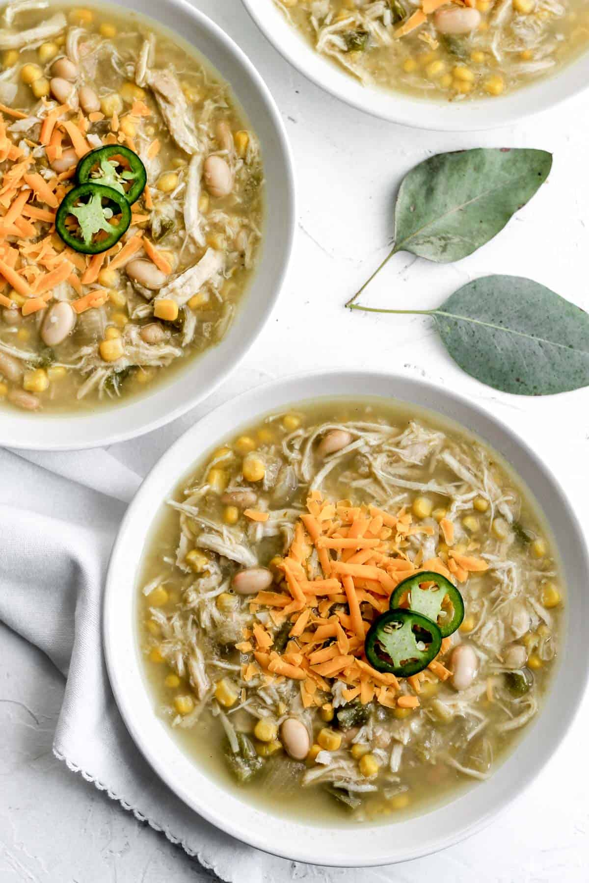 White chicken chili in 2 white bowls with a white napkin and 2 eucalyptus leaves next to them.