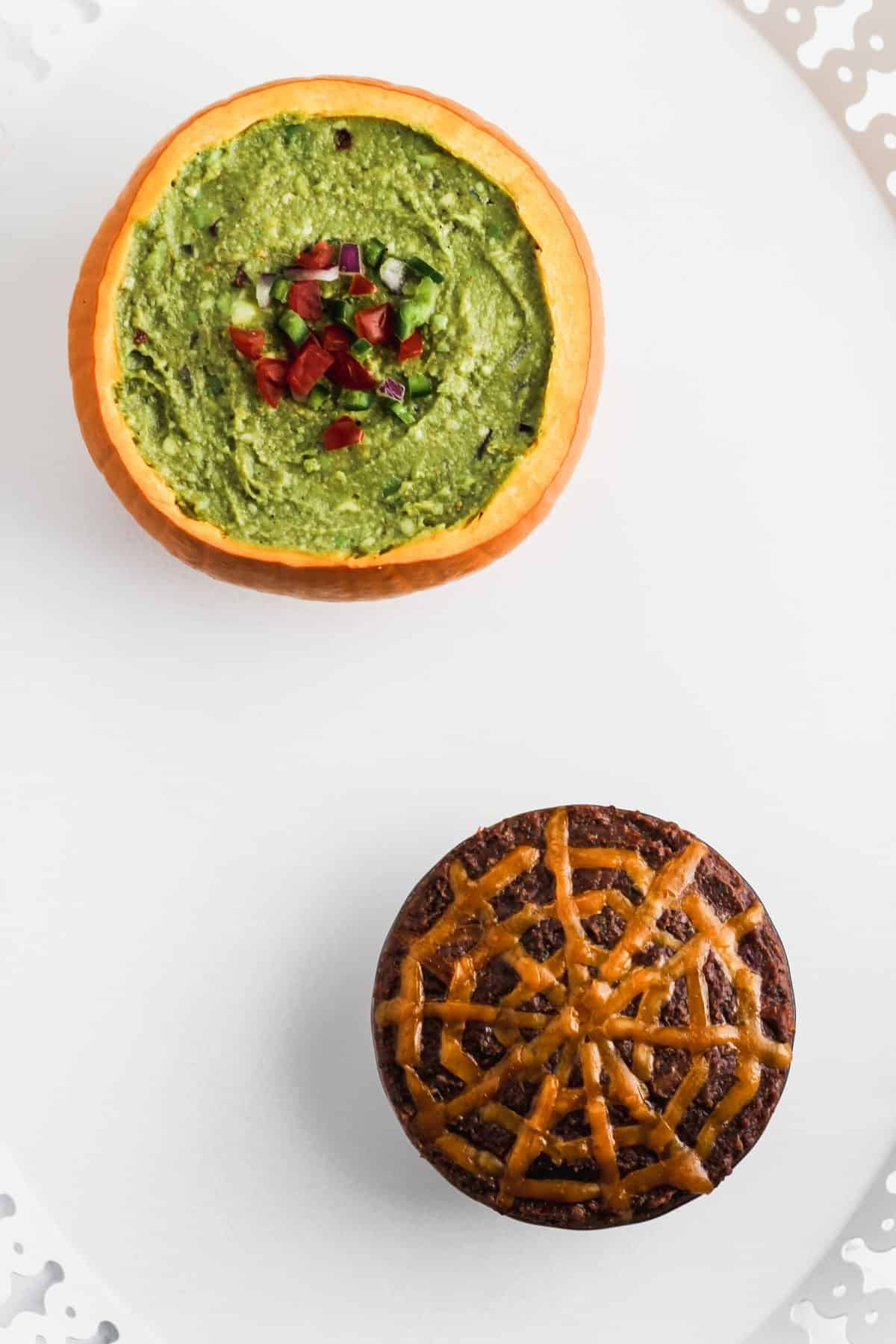 Guacamole and black bean dip in pumpkins on a white platter.
