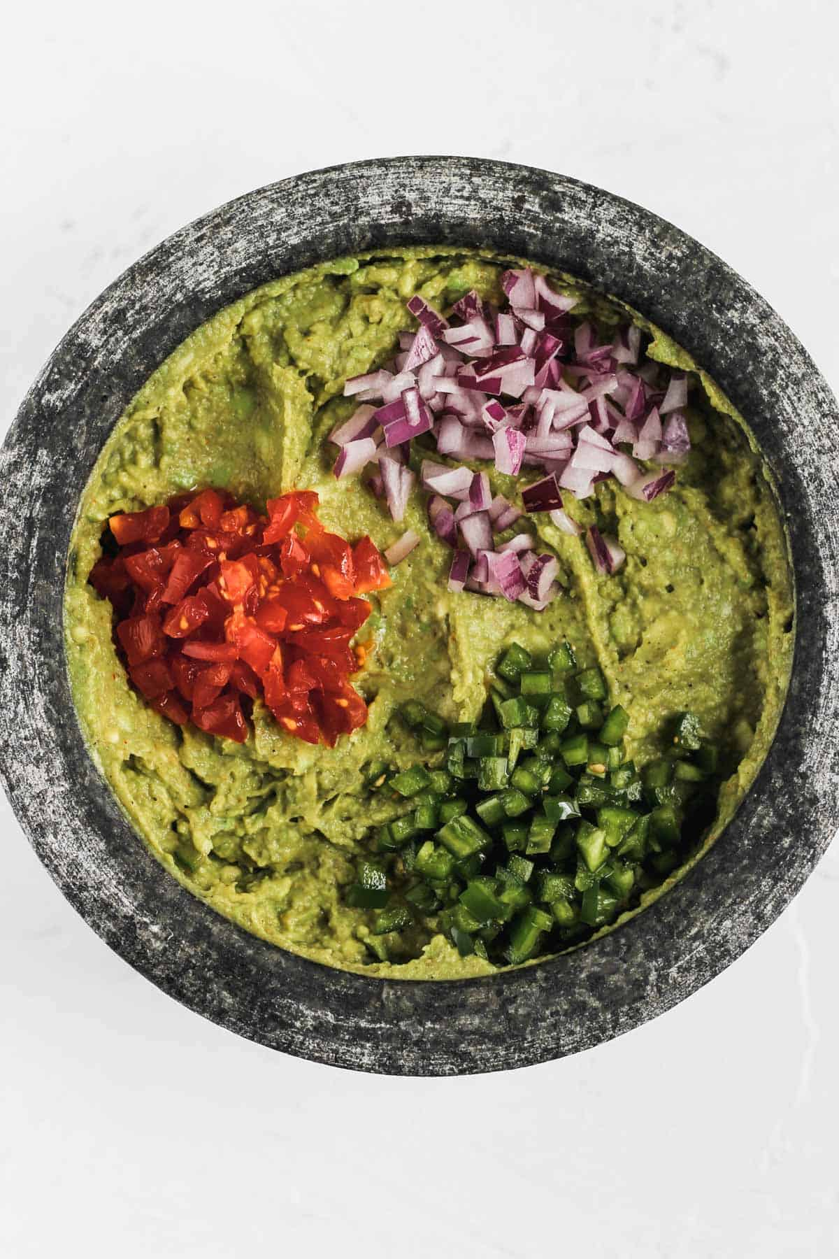 Tomatoes, red onions, and jalapeños on top of mashed avocados.