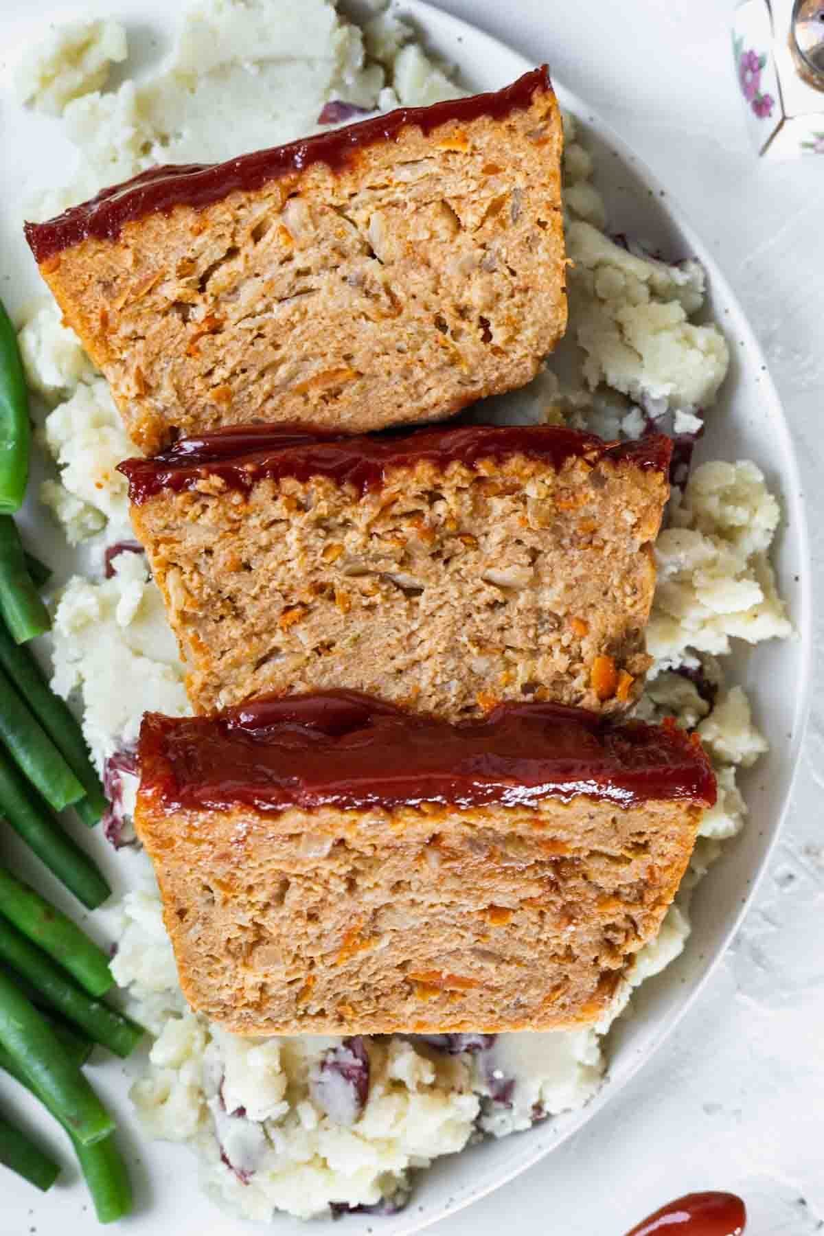 A closeup view of ground chicken meatloaf on a dinner plate with green beans and mashed potatoes.