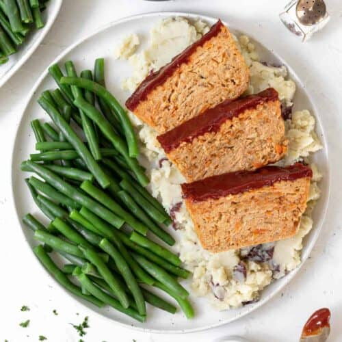 A dinner plate filled with mashed potatoes, green beans, and 3 slices of ground chicken meatloaf.