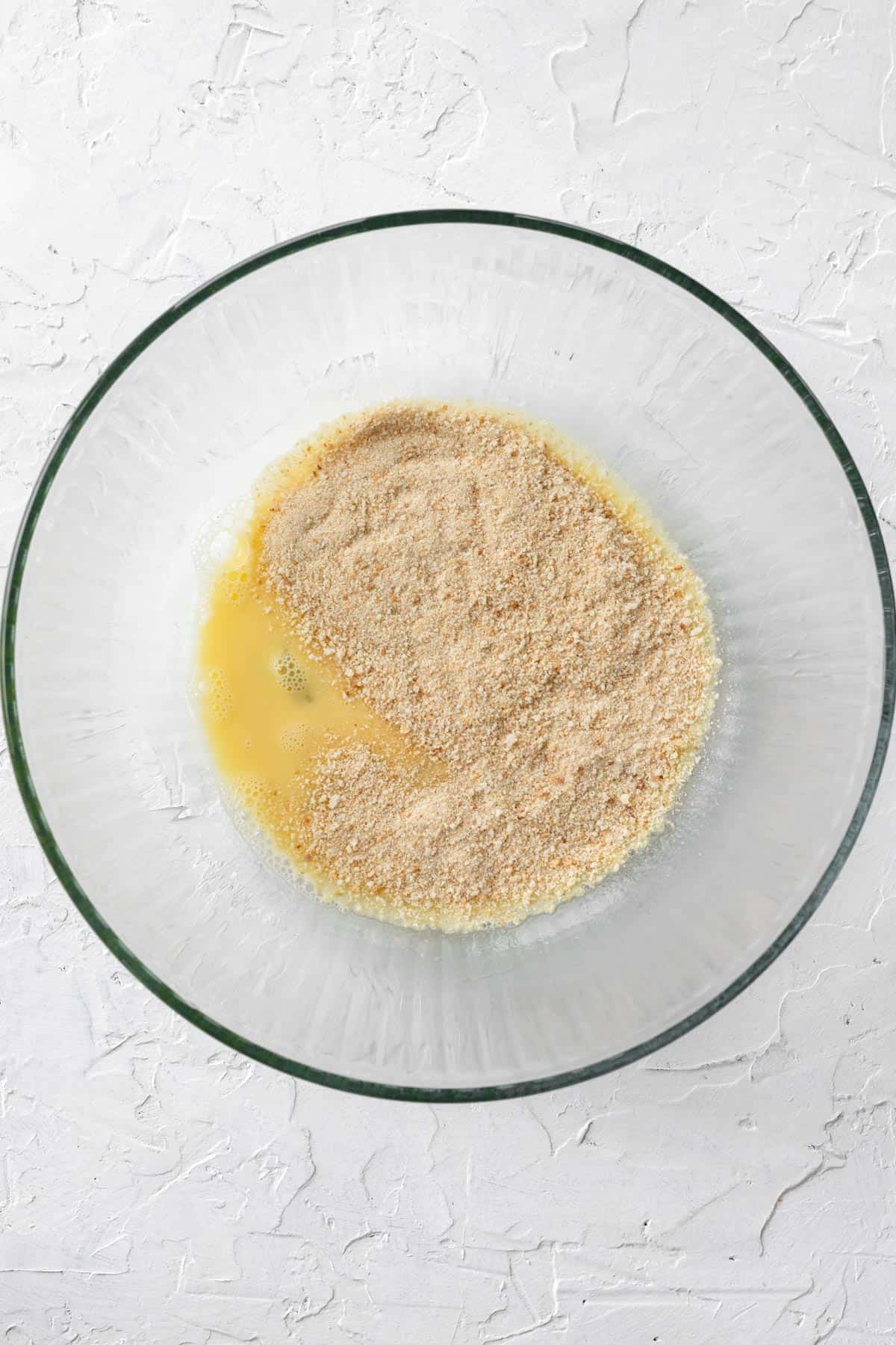 Beaten eggs topped with breadcrumbs in a glass bowl.