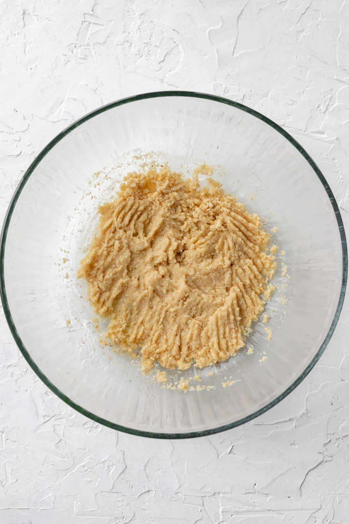 Breadcrumbs soaked in eggs and milk in a glass bowl.