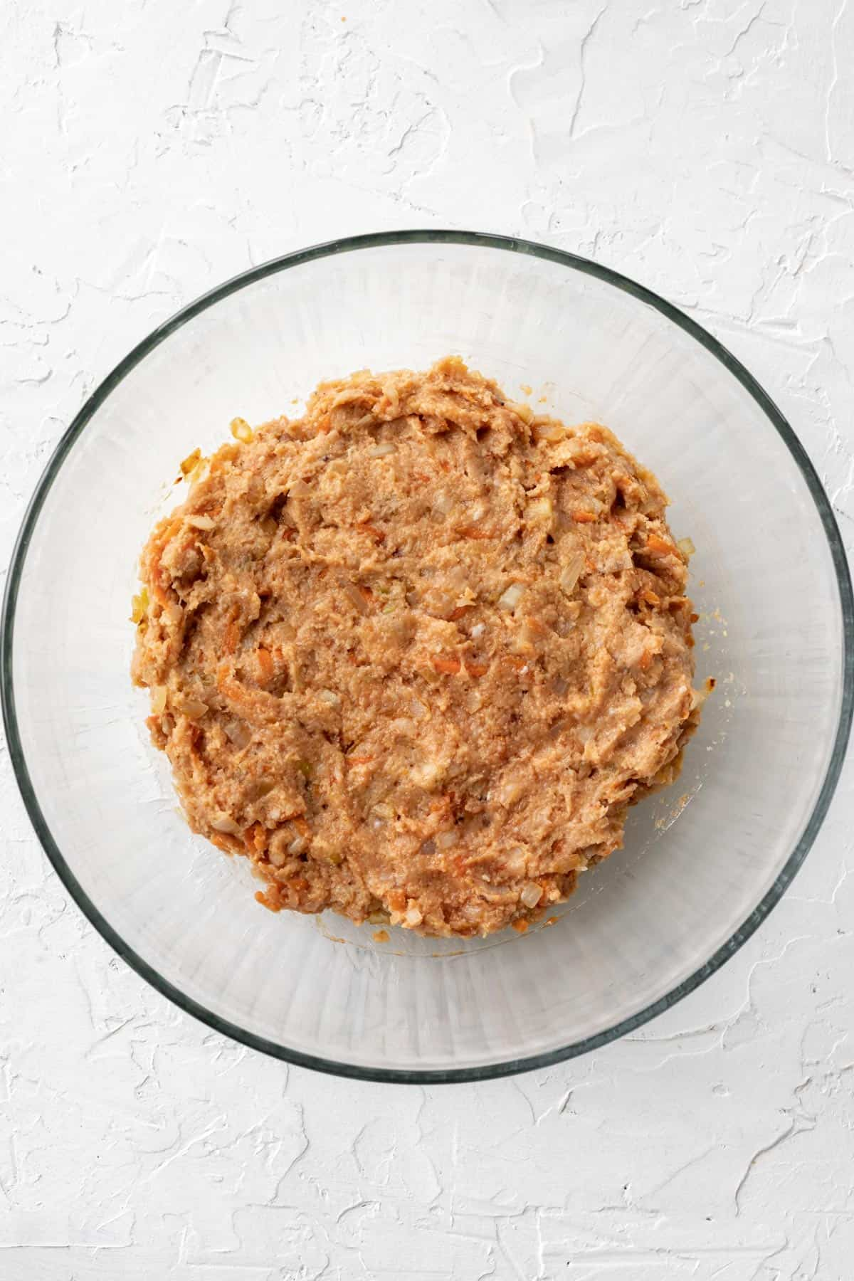 Ground chicken mixed with eggs, breadcrumbs, milk, ketchup, and vegetables in a glass bowl.