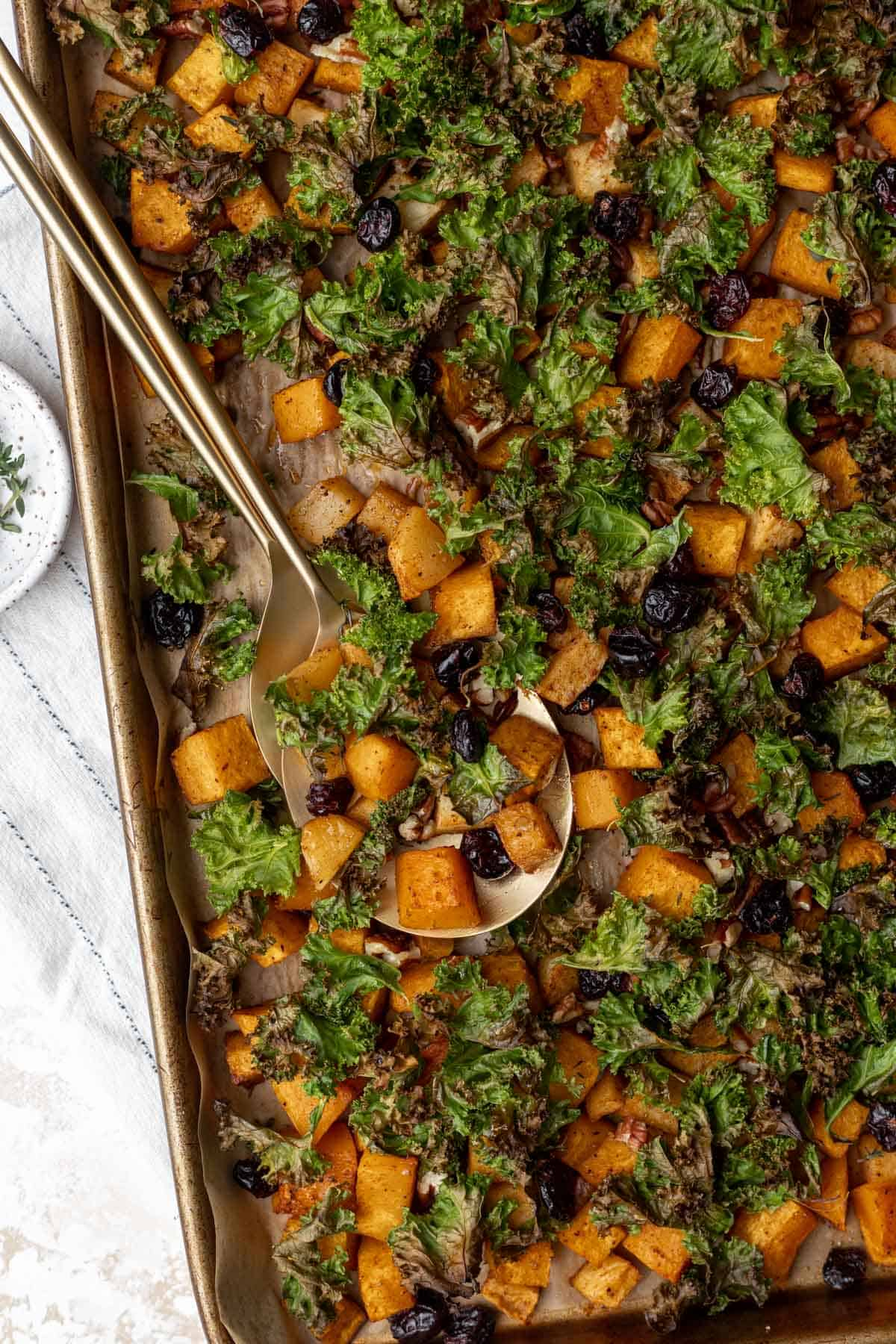 Roasted maple cinnamon butternut squash, crispy kale, baked apples, and dried cranberries on a sheet pan with two serving spoons for scooping.