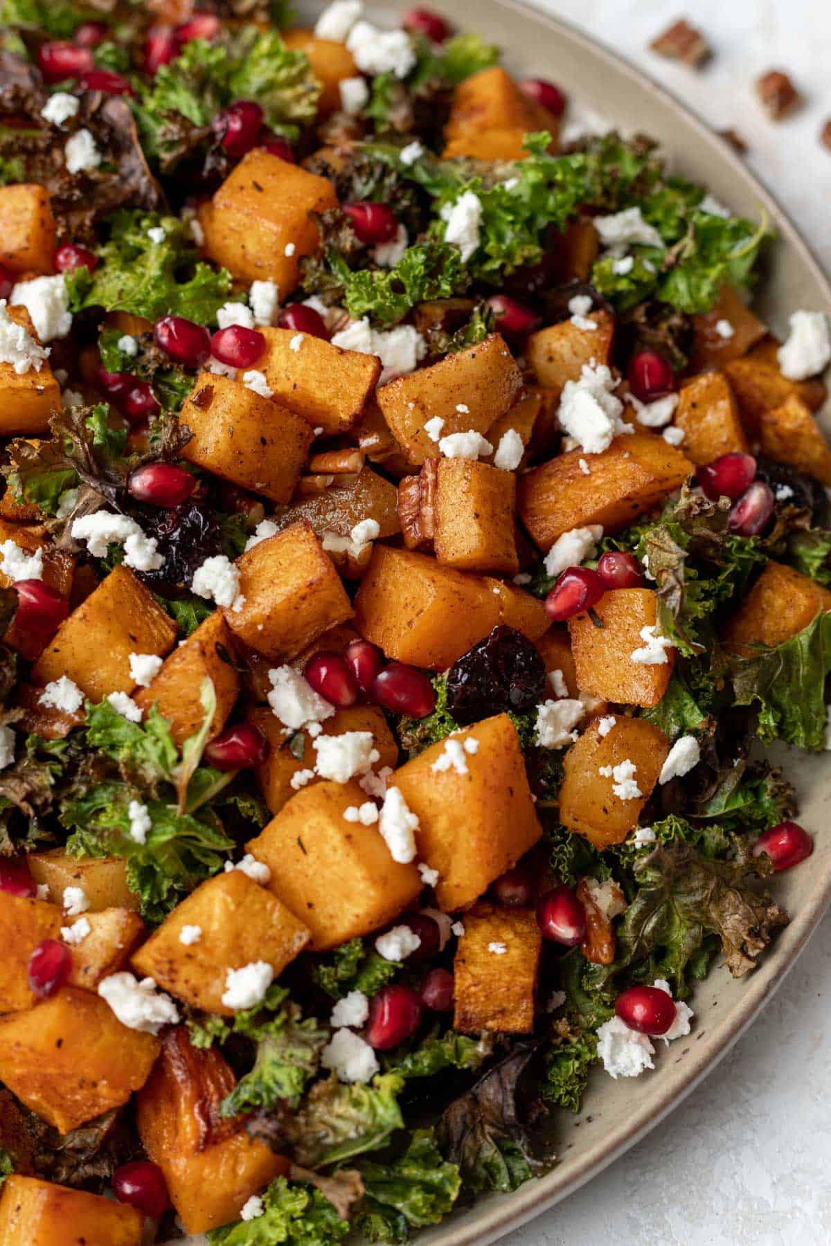 A closeup view of maple cinnamon squash, baked apples, kale chips, feta, pomegranate seeds, and toasted pecans in a beige serving bowl.