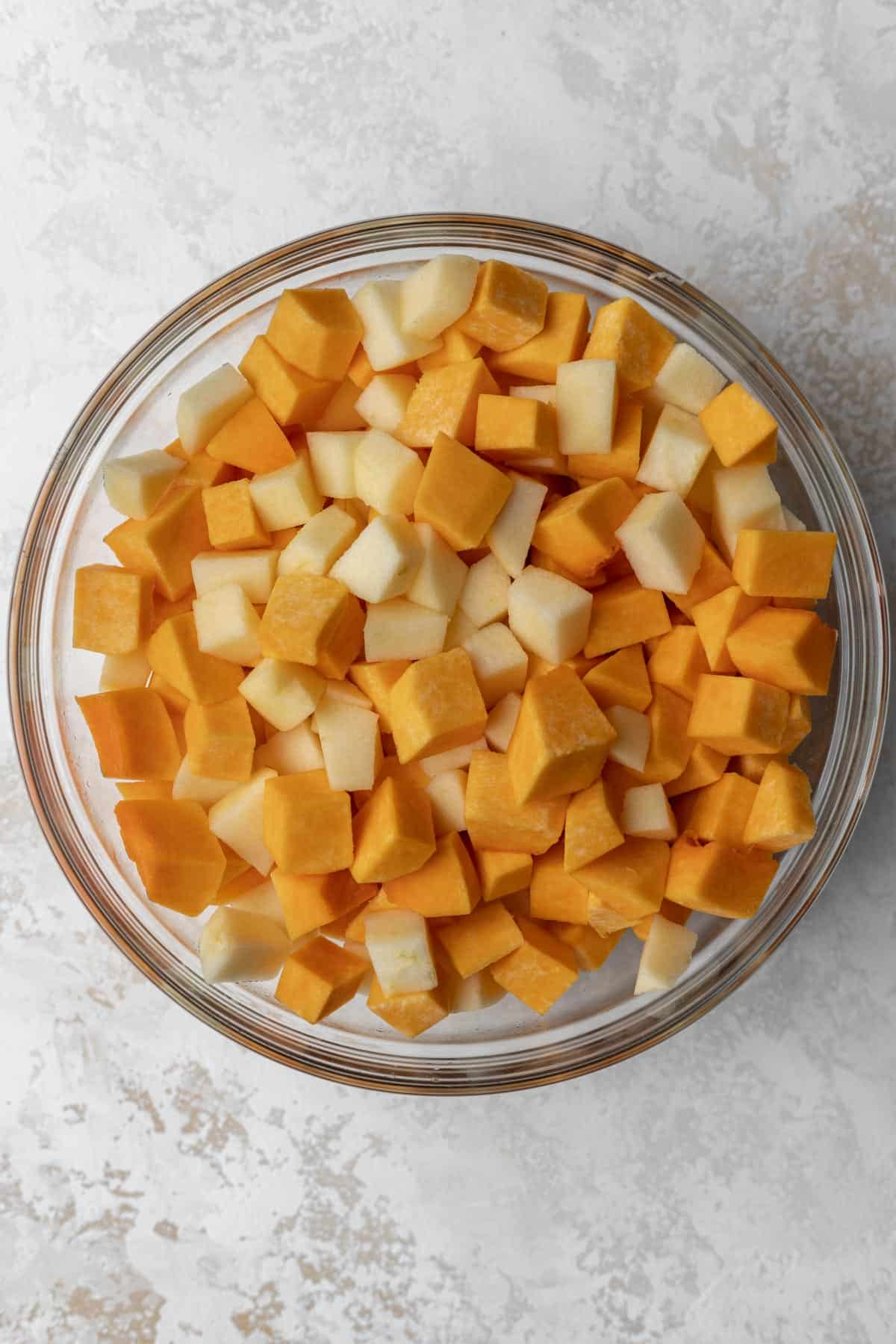 Diced and peeled butternut squash and apples in a glass mixing bowl.