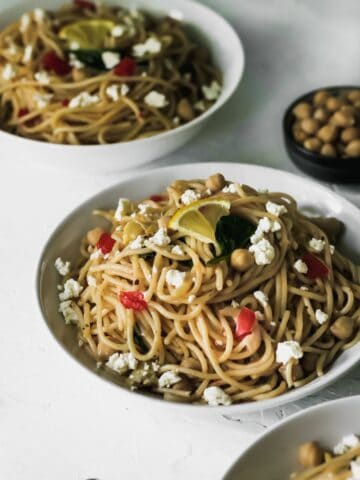 Mediterranean garlic and olive oil pasta in 3 white bowls with garbanzo beans on the side.