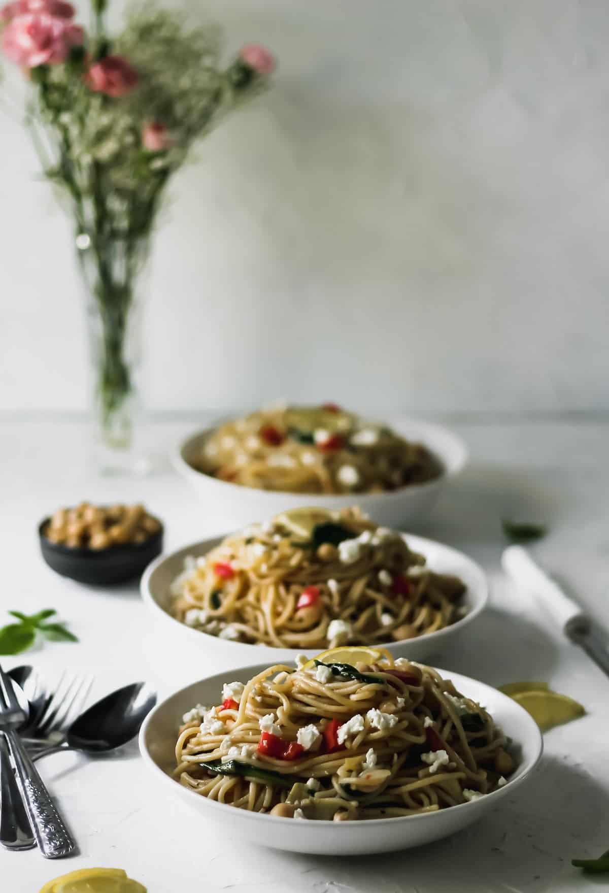 3 bowls of pasta with a vase of flowers behind them.