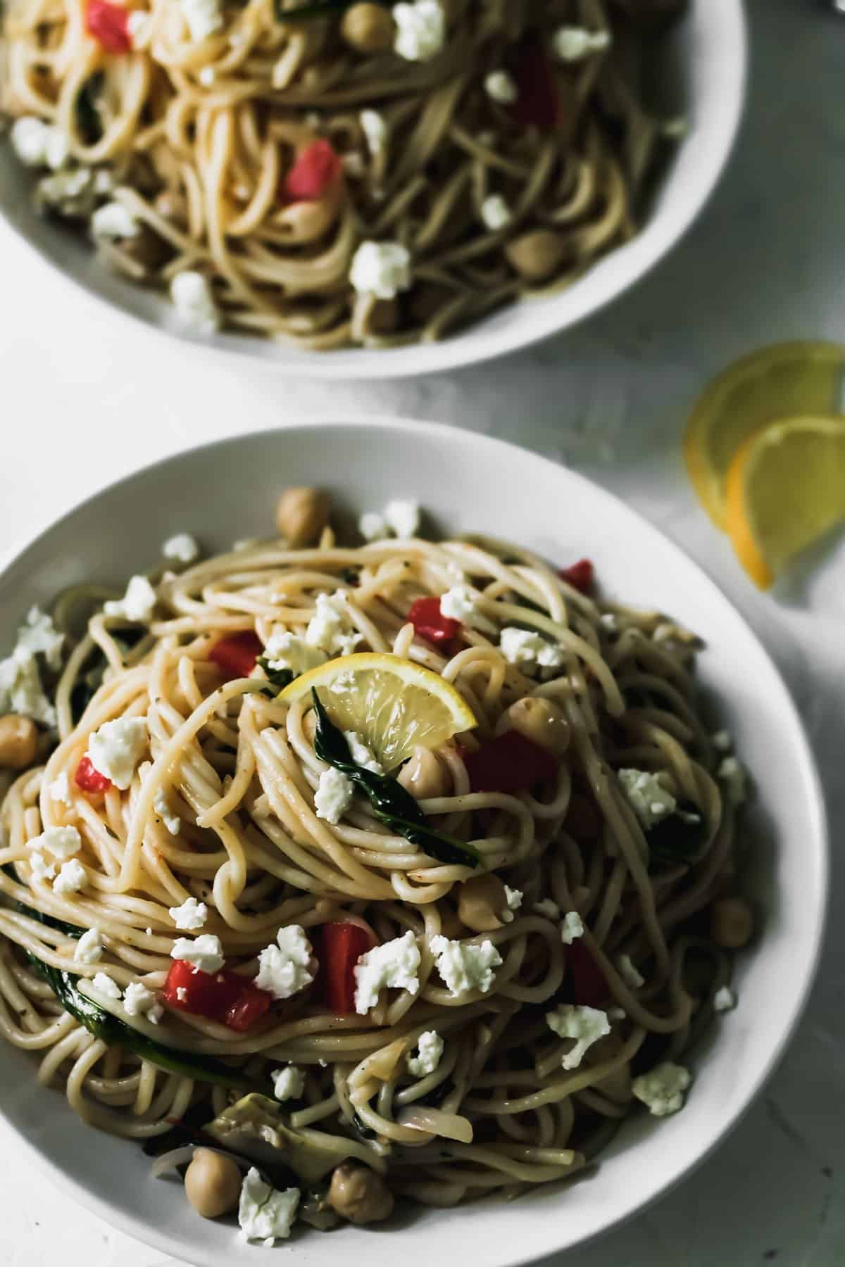 Mediterranean garlic and olive oil pasta in a white bowl with lemons on the side.