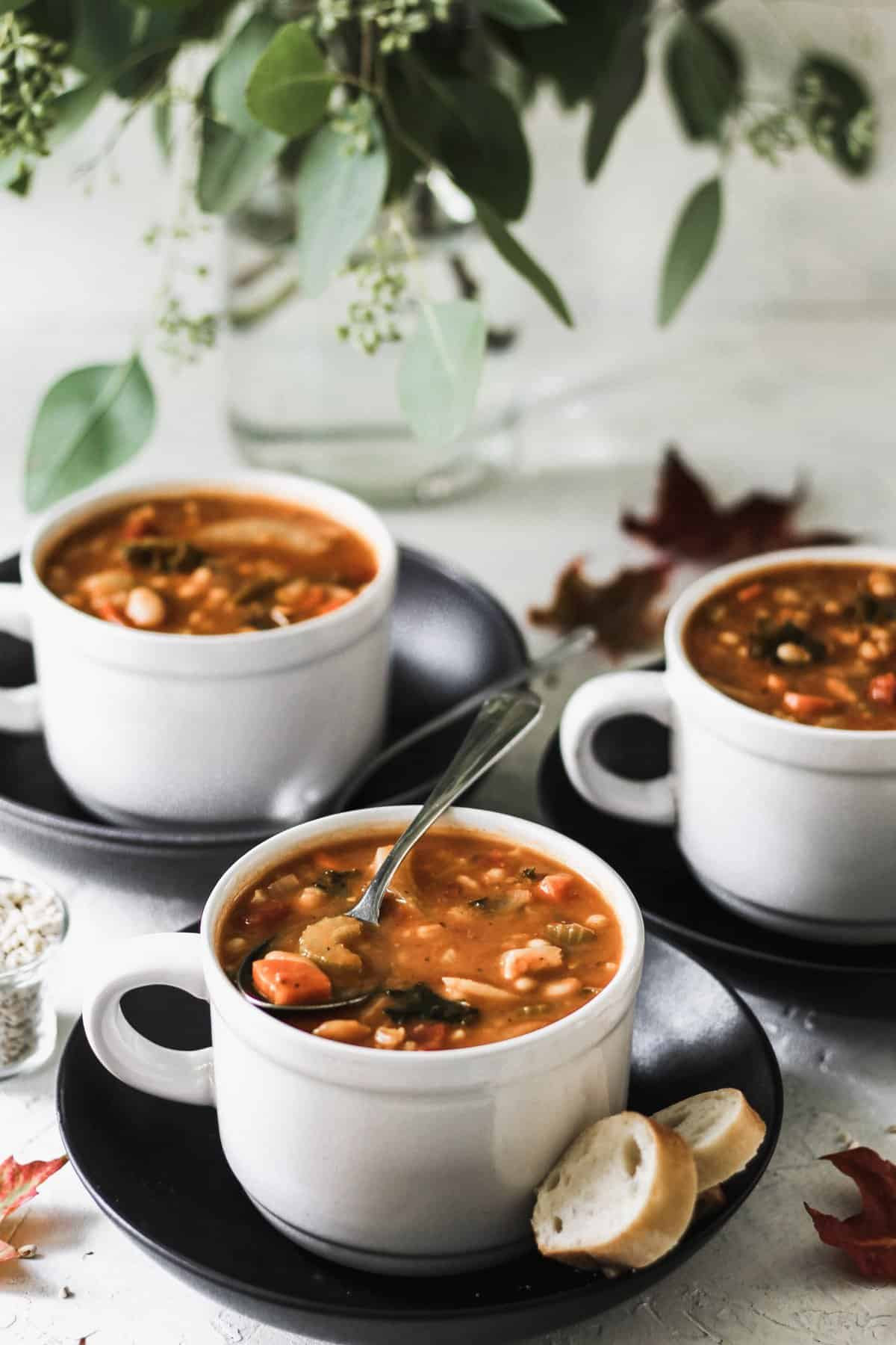 One pot vegetable bean and barley soup in 3 white mugs on top of black plates with metal spoons.