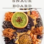 Dips, chips, chocolate almonds, carrots, peppers, and grapes on a white platter.