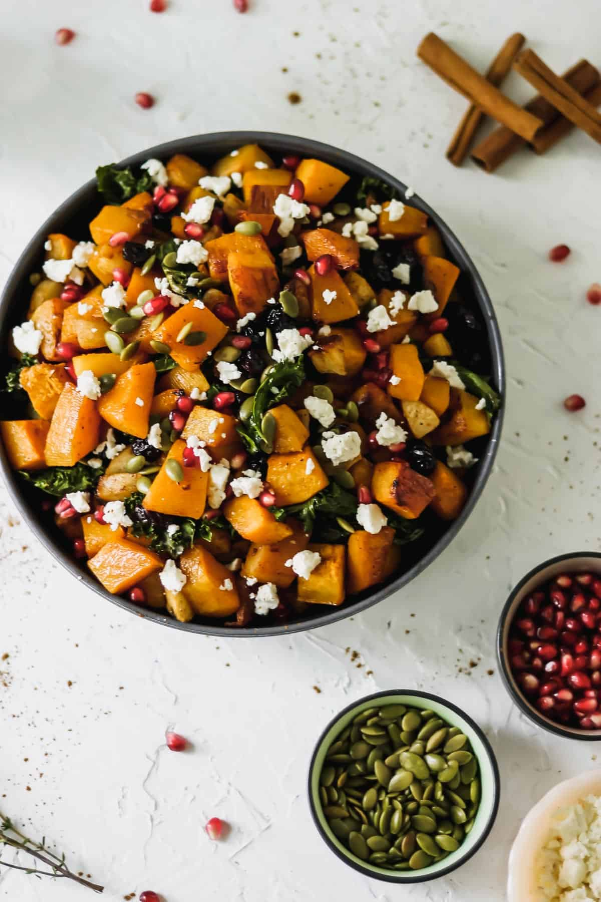 Roasted butternut squash with apples and kale in a black bowl with pumpkin seeds, pomegranate seeds, feta, thyme, and cinnamon sticks around it.