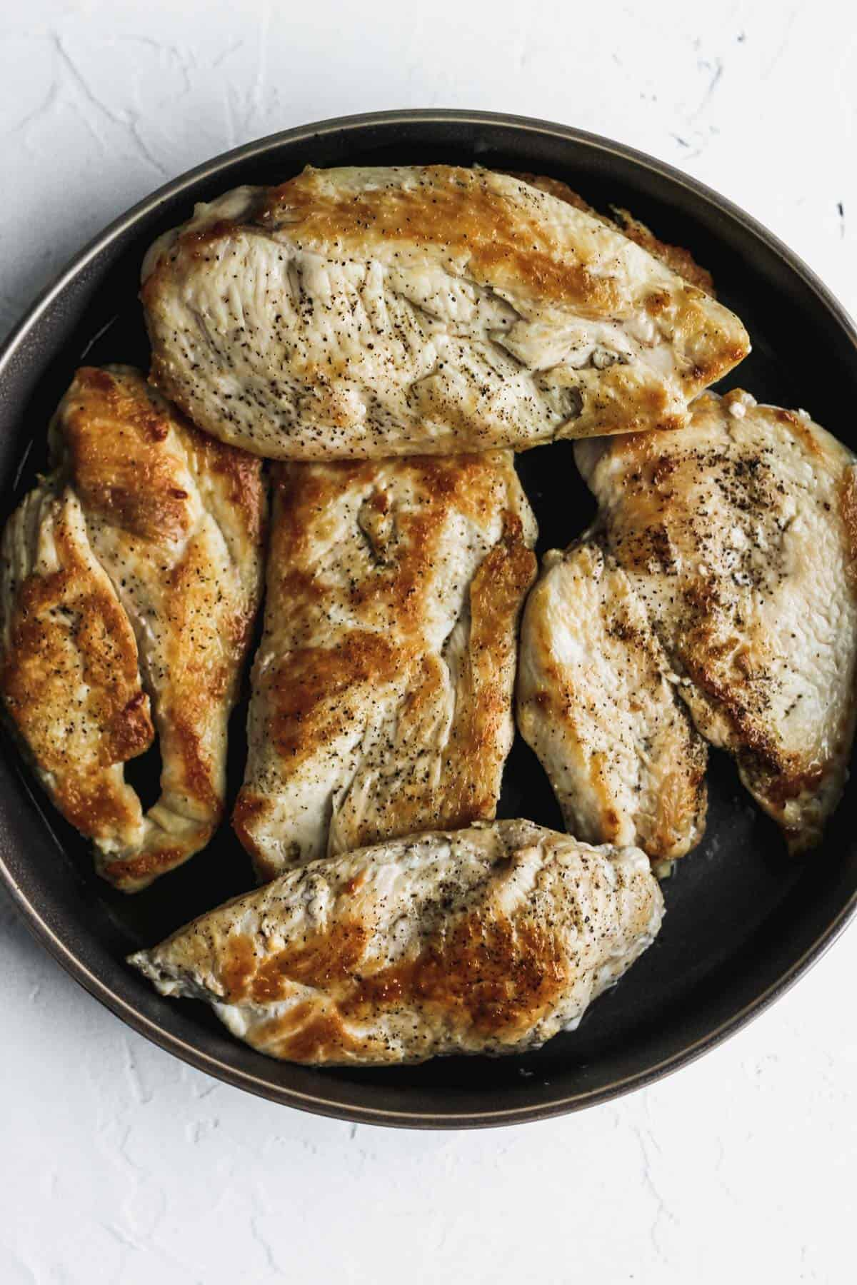 Browned and cooked chicken on a dark gray plate.