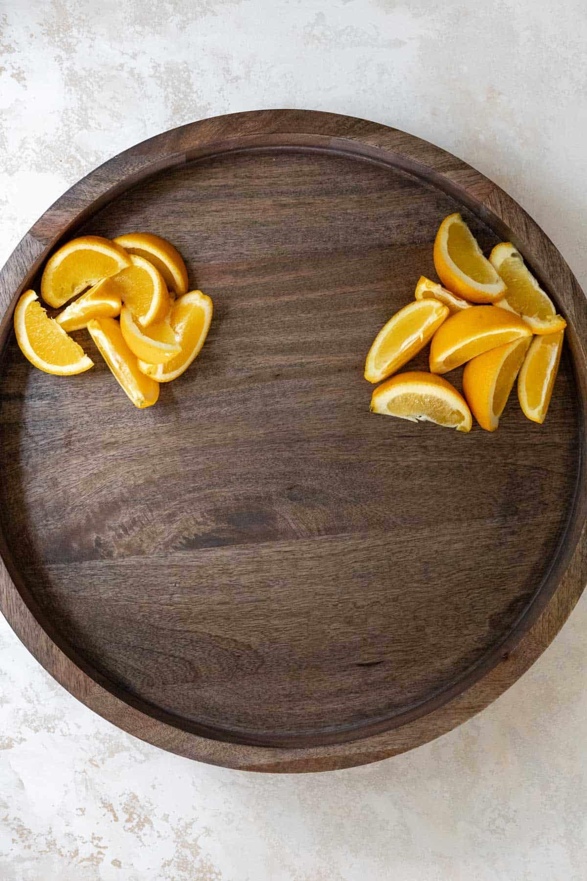 Orange wedges arranged on a wooden board.
