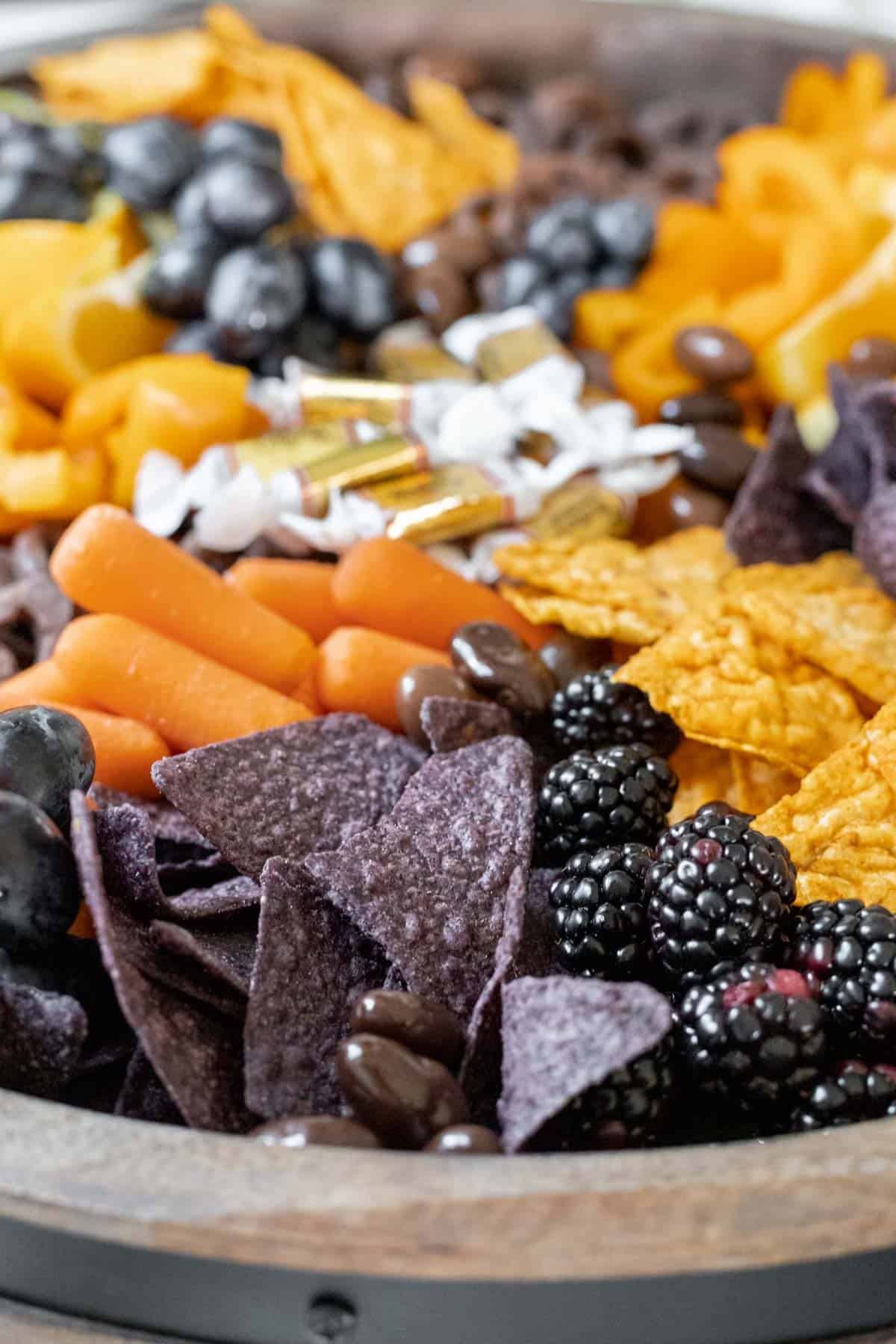 """A closeup view of all the orange and """"black"""" foods arranged on a wooden board."""