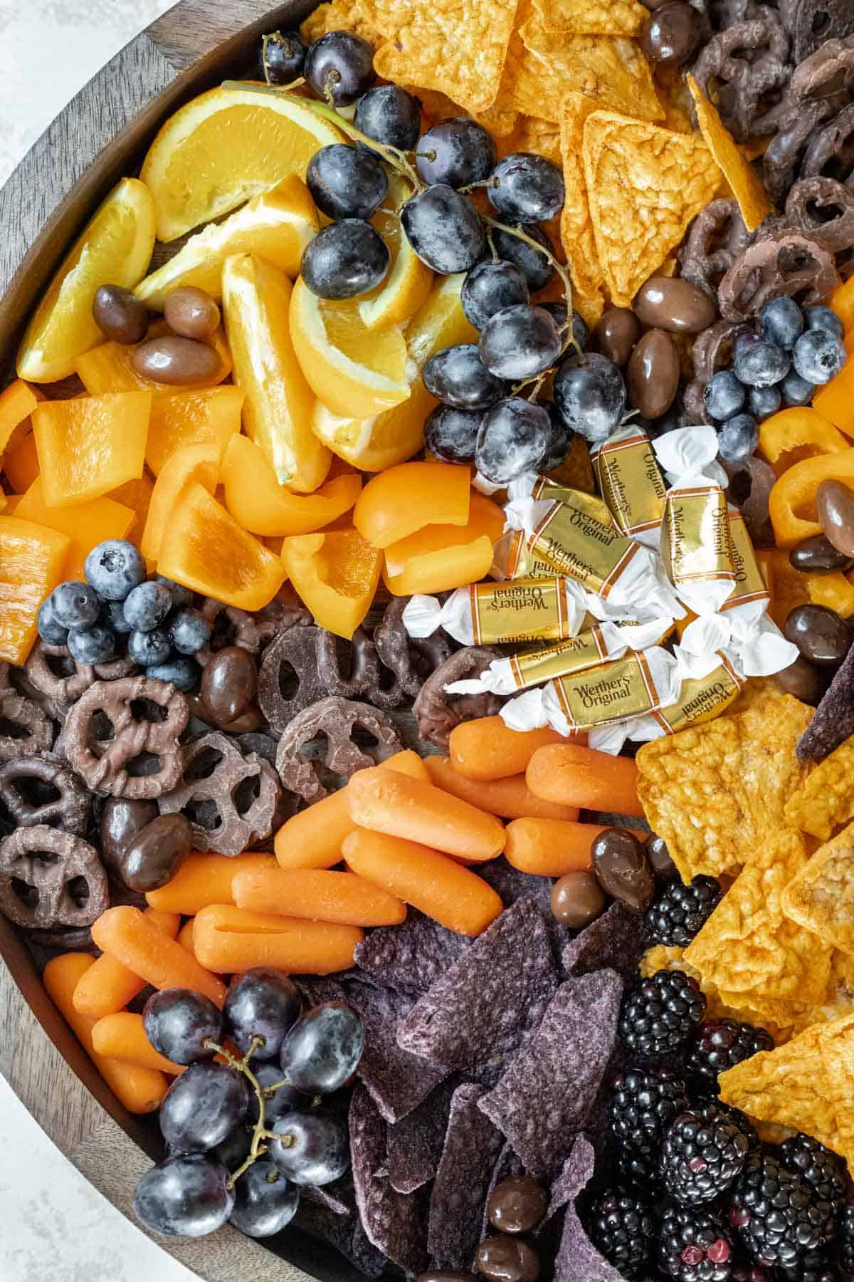 Spooky Halloween snack board with orange slices, caramels, carrots, nacho cheese chips, blue tortilla chips, chocolate pretzels, grapes, and blueberries.