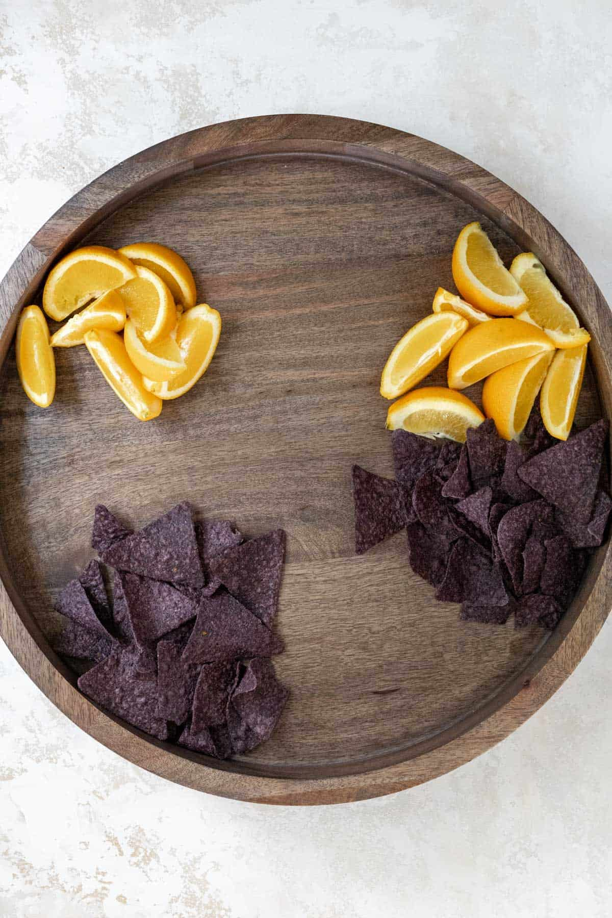 Orange wedges and blue corn tortilla chips arranged on a wooden board.