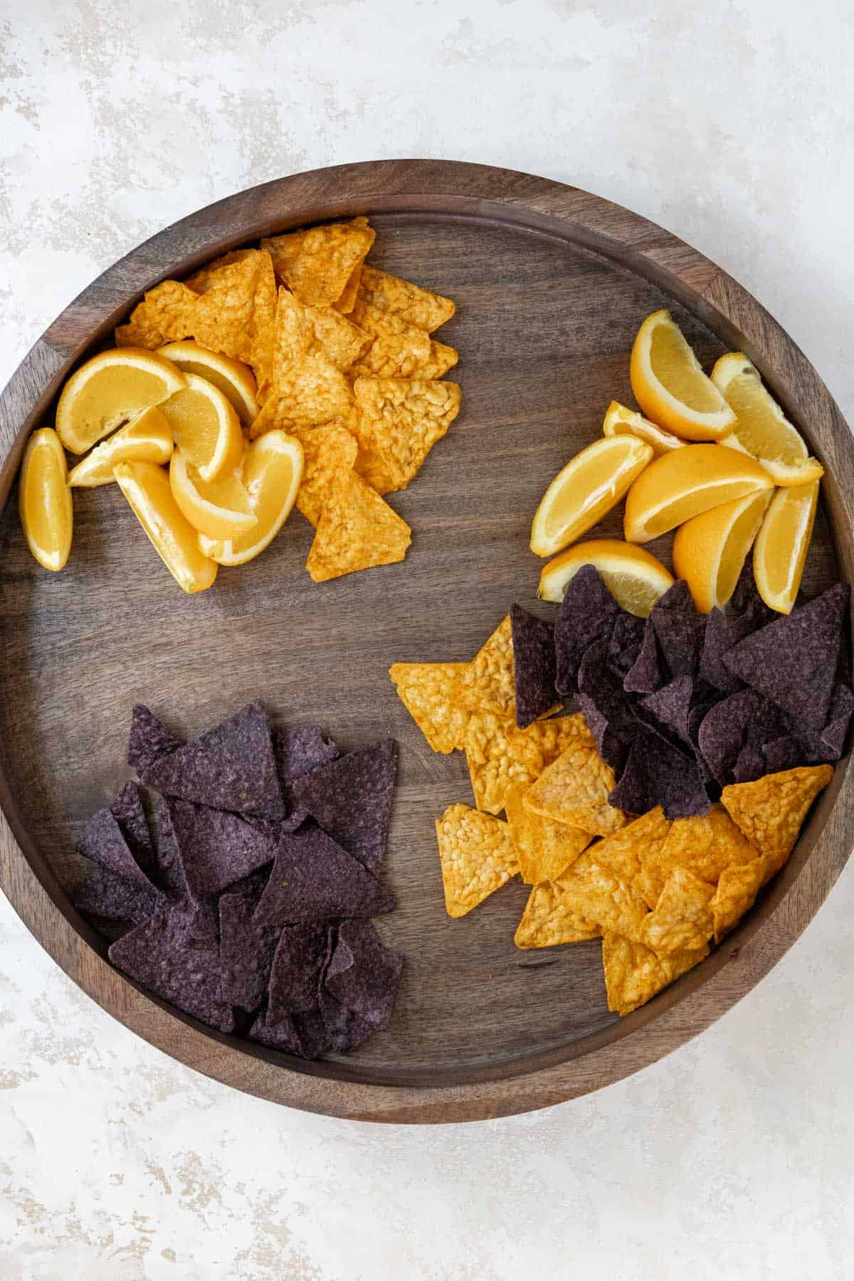 Orange wedges, blue corn tortilla chips, and nacho cheese tortilla chips arranged on a wooden board.
