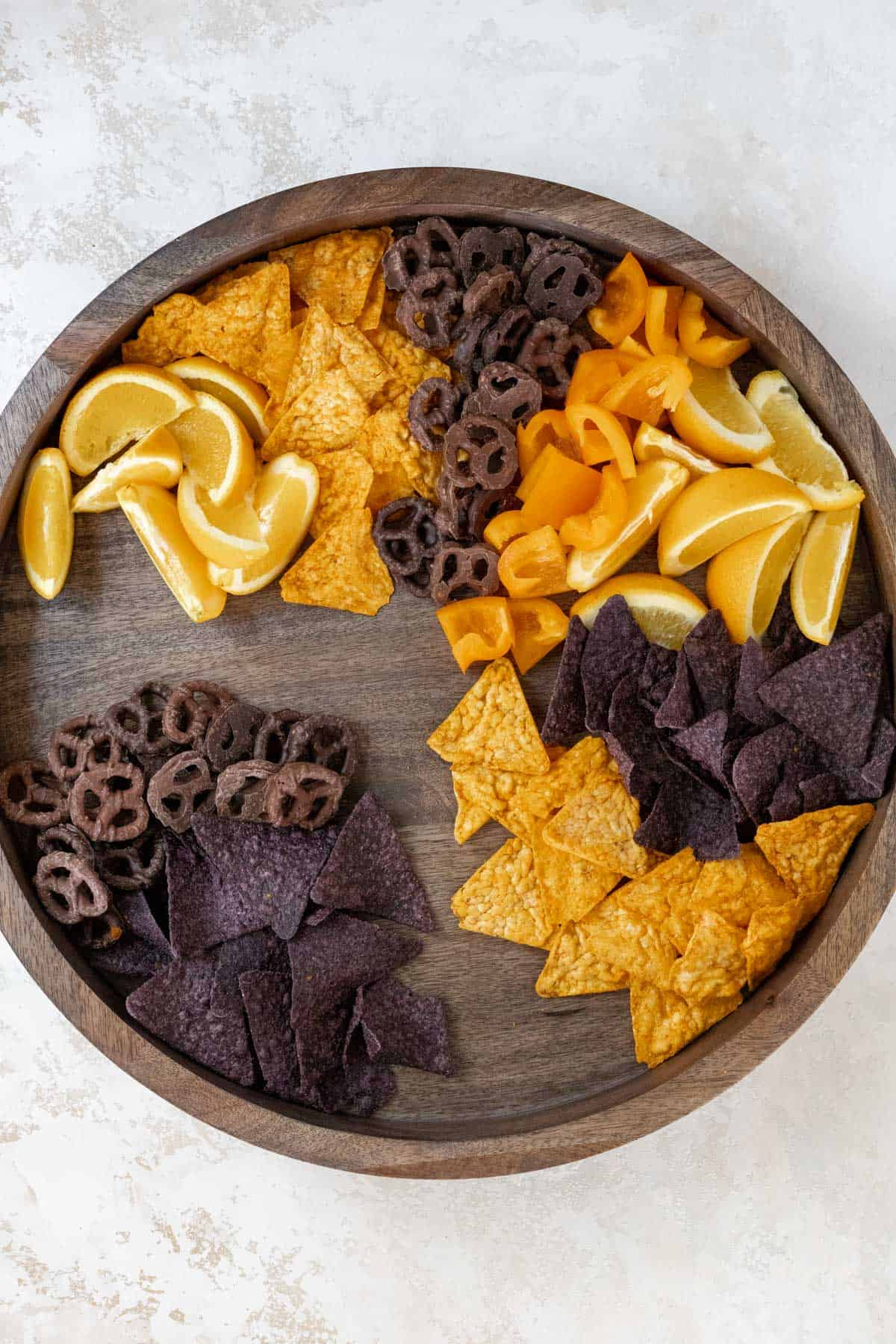 Oranges, chips, orange bell peppers, and chocolate covered pretzels arranged on a wooden board.