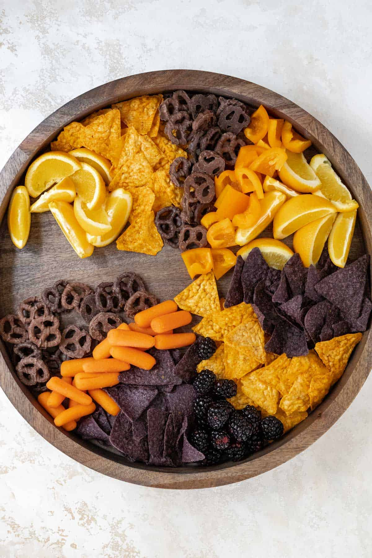Oranges, chips, orange bell peppers, and chocolate covered pretzels, carrots, and blackberries arranged on a wooden board.