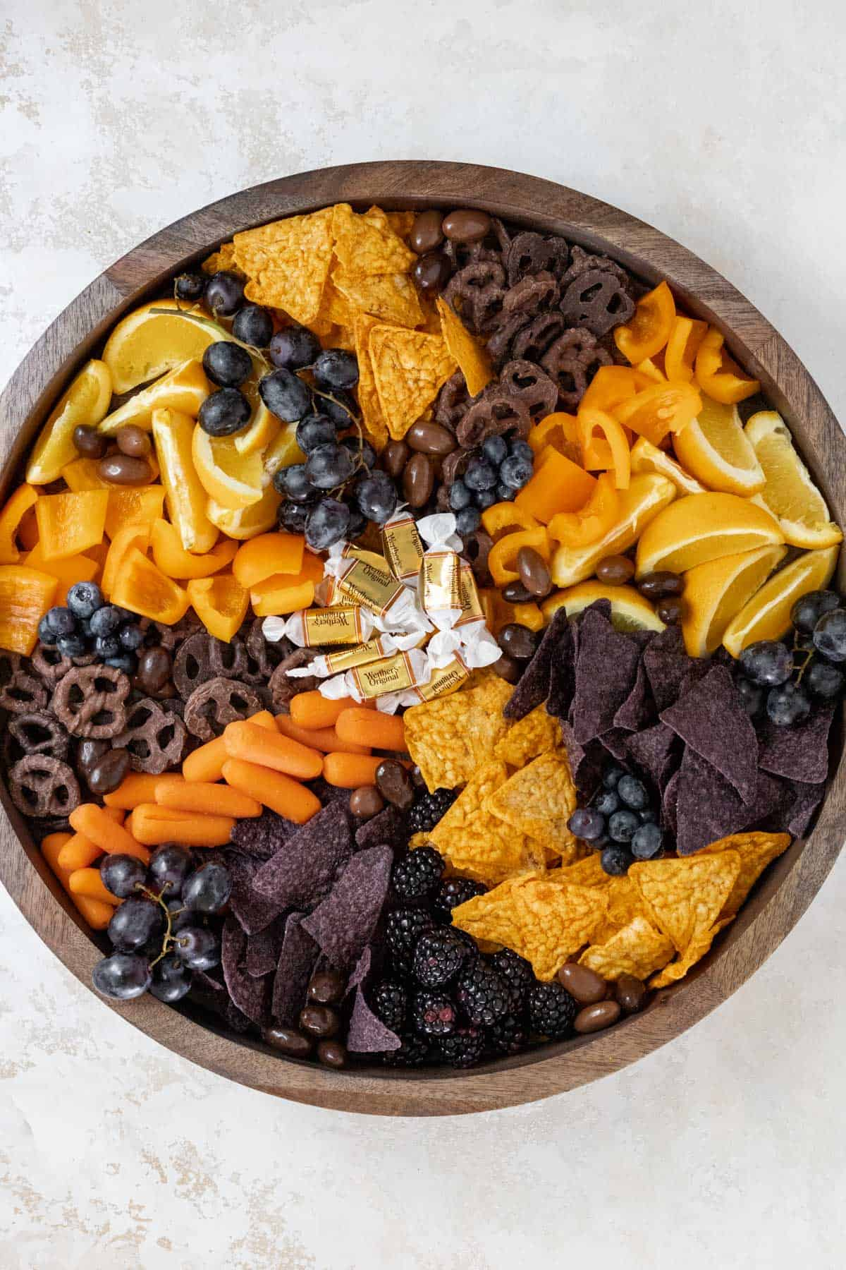 Oranges, chips, orange bell peppers, and chocolate covered pretzels, carrots, caramels, blueberries, blackberries, and chocolate almonds arranged on a wooden board.