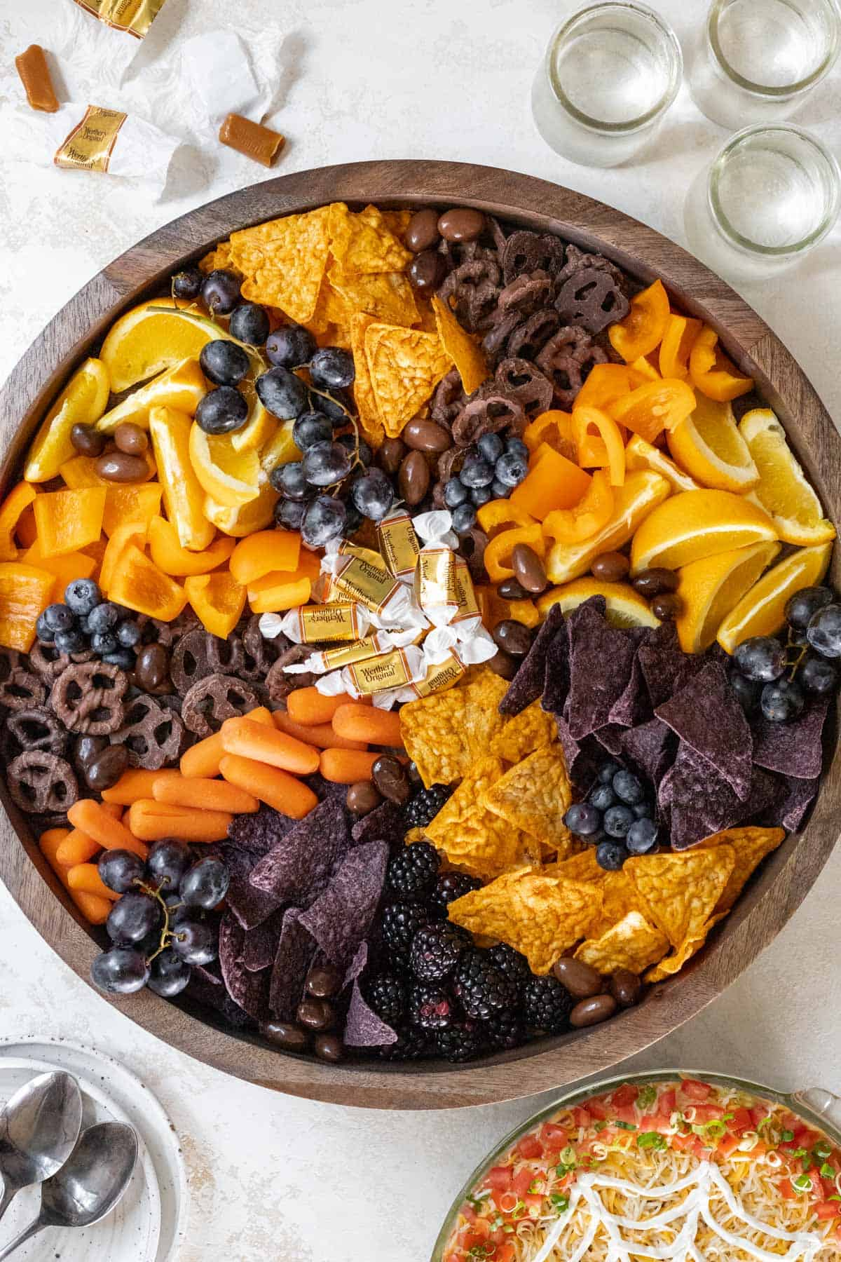 A halloween snack board on a wooden board with drinks and taco dip off to the side.